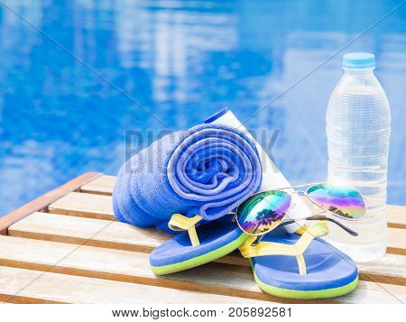 flip flops sunglasses and blue towel at the side of swimming pool. Vacation beach summer travel concept