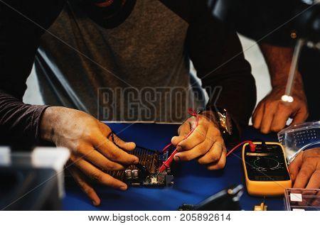 Closeup of multimeter measuring computer circuit board