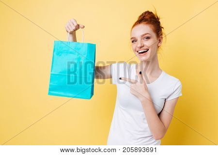 Happy ginger woman holding packet and pointing at him over yellow background