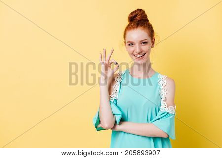 Happy ginger woman in dress showing ok sign and looking at the camera over yellow background