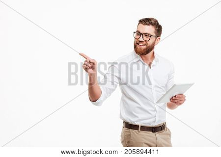 Picture of cheerful young bearded man standing near copyspace over white wall background isolated. Looking aside using tablet computer pointing.