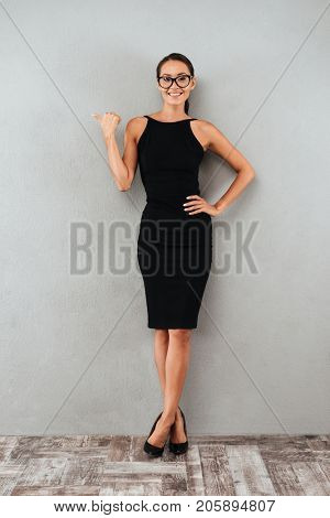 Full length portrait of a smiling pretty businesswoman in black dress and eyeglasses standing and pointing finger away at copy space isolated over gray background