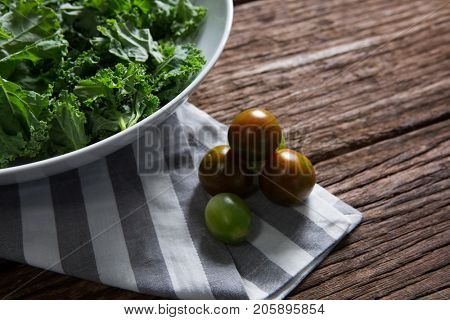 Close-up of mustard greens and gooseberry on wooden table