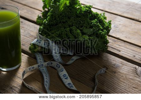 Close-up of mustard greens, measuring tape and juice on wooden table
