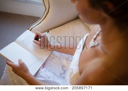 High angle view of beautiful bride writing in diary while sitting on armchair at home