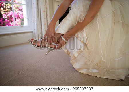 Low section of bride in weding dress wearing sandals at home