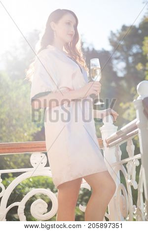 Side view of beautiful bride holding champagne flute while standing by railing in balcony