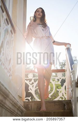 Low angle portrait of beautiful bride holding champagne flute moving down on steps