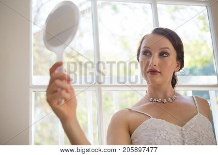 Low angle view of beautiful bride looking into hand mirror while standing by window at home