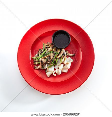 Teppanyaki Japanese and Korean Grill Food - Squid with vegetables mushrooms on sauce on  red plate on a white isolated background. Asian menu. Top View