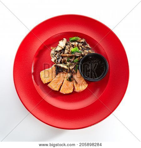 Teppanyaki Japanese and Korean Grill Food - Salmon with vegetables mushrooms on sauce on red plate on a white isolated background. Pan Asian menu. Top View