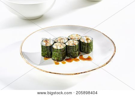 Maki rolls with tamagoyaki served on white flat plate. Asian menu for gourmets in luxury restaurant