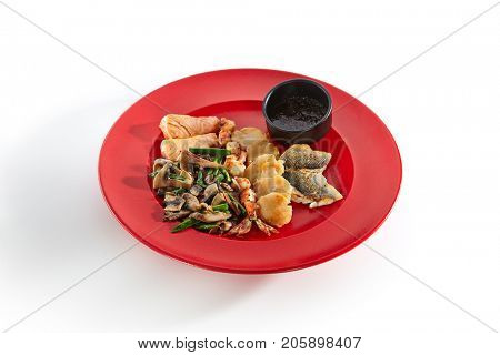 Teppanyaki Japanese and Korean Grill Food - Salmon, sea bass, shrimp 6/8, sea scallop garnished with vegetables sauce and spices on red plate on white isolated background. Asian menu