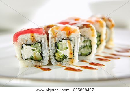Rainbow sushi rolls with salmon, tuna, eel, Philadelphia cheese and cucumber served on white flat plate. Asian menu for gourmets in luxury restaurant
