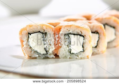 Philadelphia Classic rolls with salmon and Philadelphia cheese served on white flat plate. Asian menu for gourmets in luxury restaurant