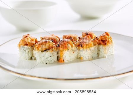 Baked rolls with crab, creamy cheese and avocado with rice on white plate with gold border. Asian restaurant menu