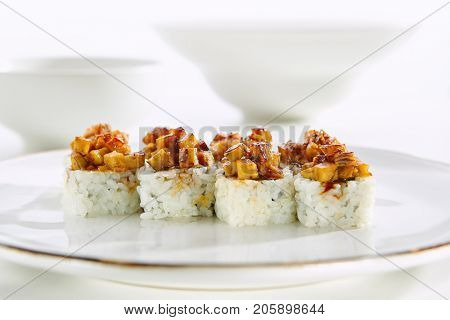 Baked rolls with tamagoyaki and rice on  white plate with gold border. Asian restaurant menu