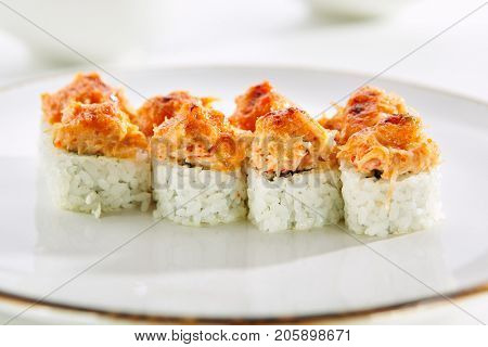 Baked rolls with salmon, creamy cheese, green onion and rice on white plate with gold border. Asian restaurant menu