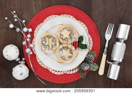 Christmas mince pies with holly on a porcelain plate with holly, fir, fork, cracker and bauble decorations on a red place mat on oak wood background.