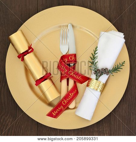 Christmas table place setting with gold dinner plate, cutlery with red ribbon, napkin with cedar and cracker on oak table background.