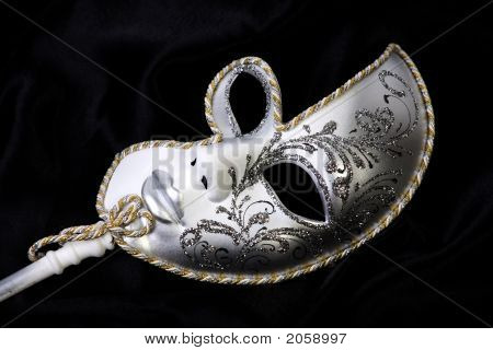 ornate venician mask pictured against a black background poster