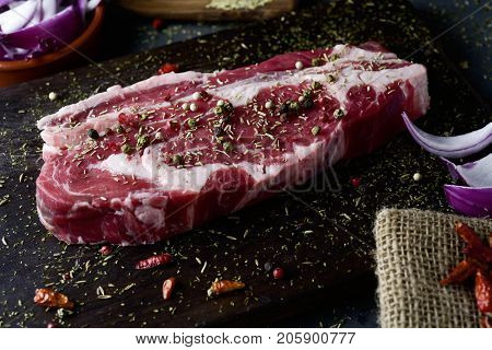closeup of a raw strip steak seasoned with different spices, such pepper corns of different colors or oregano, on a rustic dark wooden tray