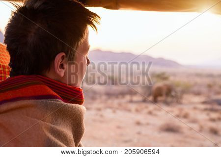 Teenage boy on safari covered with warm blanket outdoors on beautiful morning safari game drive