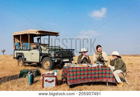 Family of mother and kids on African safari vacation enjoying bush breakfast