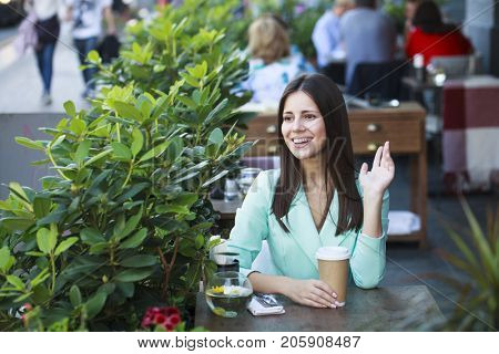 Young beautiful girl sitting in a cafe welcomes waving her hand in a restaurant outdoors
