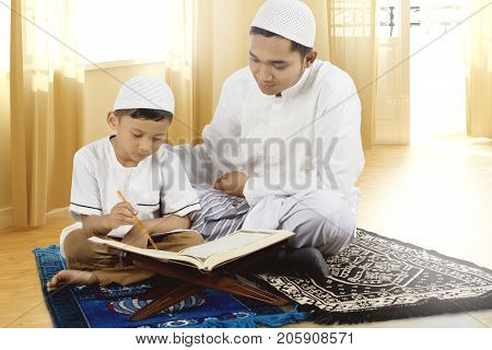 Son learns to read Quran with his father while sitting on prayer carpet together at home