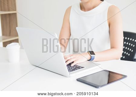 Attractive women in casual business sitting at a table working on her laptop computer at home office in front of a window