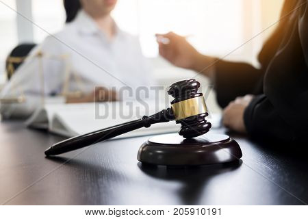 Judge gavel with lawyers advice legal at law firm in background. Concepts of law services.