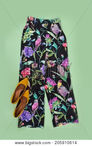 floral trousers,pants with yellow shoes on green background