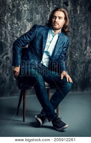 Fashion shot of a handsome man posing on a chair at studio. Furniture and interior. Male beauty, fashion.