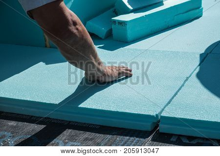 Worker placing XPS polystyrene insulation boards on the flat roof