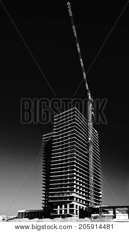 Crane and building under construction in Tel-Aviv. Industrial construction crane in Israel. Black and white picture