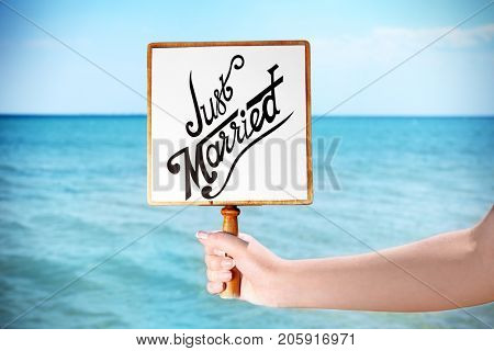 Woman holding wooden board with text JUST MARRIED on blue sea background. Beach wedding concept