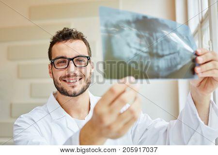 Radiologist holding x-ray image of denture