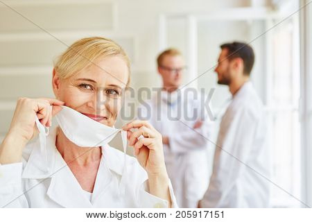 Woman doctor putting surgical mask on getting ready for surgery