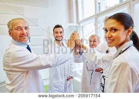Team of doctors High Five as teamwork and motivation