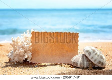 Composition with blank card, coral and sea-urchins on sand. Beach wedding concept