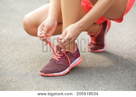 Young sporty woman tying shoelaces outdoor