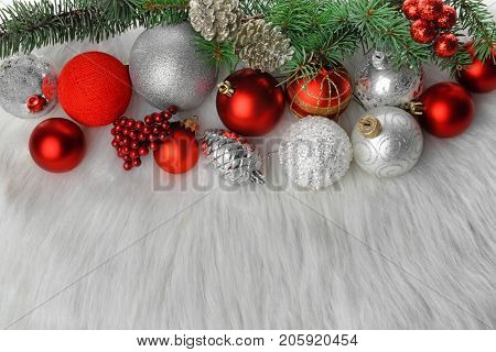Beautiful composition with Christmas decorations and brunches of fir tree on soft plaid