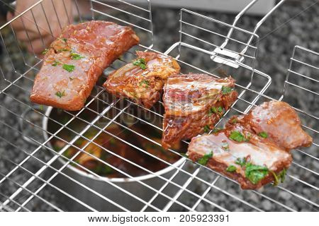 Appetizing juicy spare ribs on bbq grid outdoors