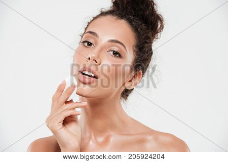 Close up beauty portrait of a sensual brunette woman with soft healthy skin removing make up with cotton pad isolated over white background