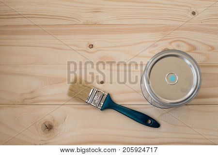 Blue paint and brush on wooden background, top view. Home improvement paint brush and opened can blue paint. Bank blue paints and brush on a wooden background. brush and paint  on a wooden background.