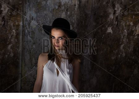 A girl in a white blouse, a black hat. with tare destroyed building. Helouin.