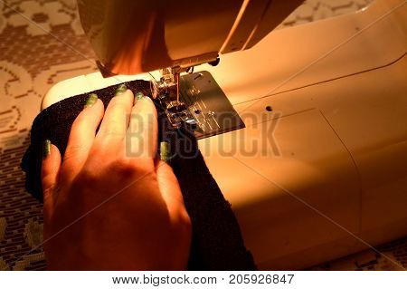 Sewing machine, seamstress sewing at machine and women's hands.  Young Woman  Working On Sewing Machine. Fashion. Female hands on sewing machine.
