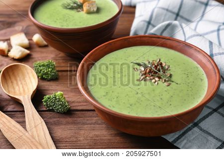 Bowl with delicious broccoli soup on table