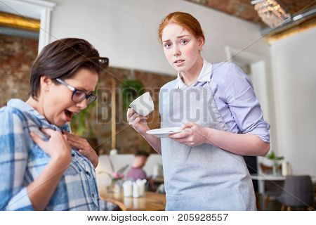 Embarrassed waitress with cup and saucer looking at camera with displeased guest near by